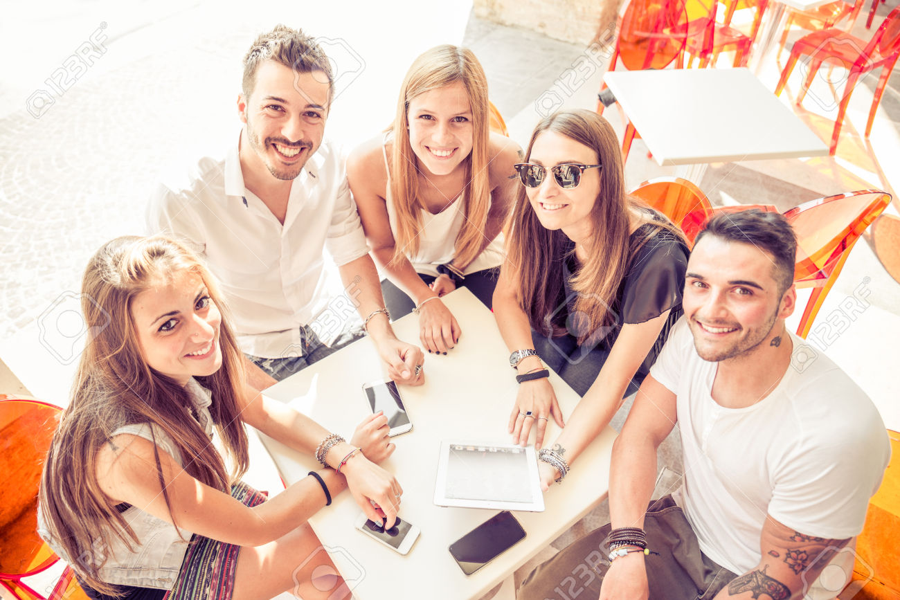 40823015-Group-of-happy-and-smiling-friends-sitting-in-a-bar-and-looking-at-the-camera-many-digital-devices-o-Stock-Photo.jpg